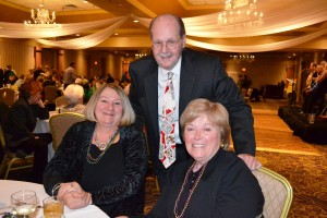 (From l-r) Dee Hennemuth celebrates with UNC board members Atty. Drew Hailstone and Elizabeth Burns at United Neighborhood Centers' 14th Annual Mardi Gras Celebration.