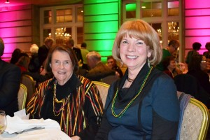 UNC board member Jane Oppenheim (left) Dede Tersteeg got into the spirit of Mardi Gras with beads and New Orleans style food.